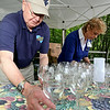 Daniel Vineyards owner C. Richard Daniel lays out wine glasses for incoming patrons as his longtime employee Kay Pence, right, helps out Saturday afternoon during the Daniel Vineyards Spring Wine Festival in Crab Orchard. Wine tasting, food and live music were all a part of the festivities, and patrons also had a chance to get a look around the site's picturesque grounds.<br /> Brad Davis/The Register-Herald