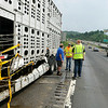 Cleanup crew members survey the damage to a cattle truck involved in an accident with another truck Friday afternoon as it was heading northbound on I-64 just about one mile past the I-77 split. Three cattle escaped after the accident, two of which had to be put down because they posed a safety threat as they roamed the active highway, while the third was still said to be on the loose somewhere nearby.<br /> Brad Davis/The Register-Herald