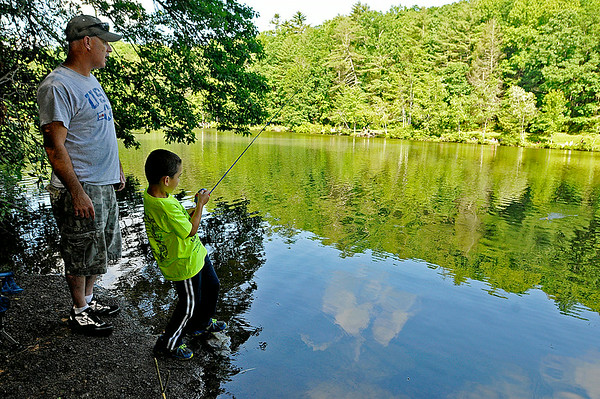 Piney View resident Daris Plumley watches as his son Austin, 6, reels in his line in excitement after feeling a couple of bites during the 23rd Annual Kids Fishing Derby June 14 at Little Beaver State Park. Hundreds of kids 14 and under flocked to the lake area at Little Beaver, some of them already angling veterans while others were getting their first fishing experience.<br /> Brad Davis/The Register-Herald