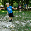 Hickory, North Carolina residents Madelyn Beisler, 8, and her brother Cayden, 6, play a game of murbles June 16 at Pipestem State Park. Here, Cayden measures the distance from his sister's ball to the point ball to see if she's really doing as good at the game as it looks like she is as their dad Cliff looks on. <br /> Brad Davis/The Register-Herald