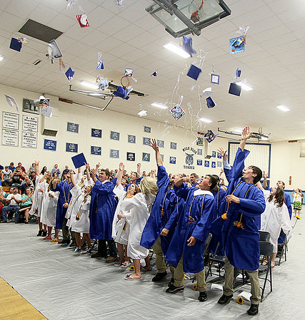 Meadow Bridge High School's graduating seniors fling their caps into the air at the conclusion of the school's commencement ceremony Saturday afternoon. Graduation season continued this weekend as friends and family members packed the Meadow Bridge gymnasium for their ceremony, while Westside and Wyoming East seniors will collect their diplomas today.<br /> Brad Davis/The Register-Herald