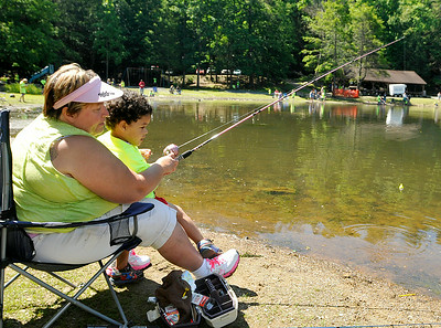Theresa Underwood introduces 2-year-old Ayden Paul to fishing during the 23rd Annual Kids Fishing Derby June 14 at Little Beaver State Park. Hundreds of kids 14 and under flocked to the lake area at Little Beaver, some of them already angling veterans while others were getting their first fishing experience. Brad Davis/The Register-Herald