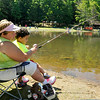 Theresa Underwood introduces 2-year-old Ayden Paul to fishing during the 23rd Annual Kids Fishing Derby June 14 at Little Beaver State Park. Hundreds of kids 14 and under flocked to the lake area at Little Beaver, some of them already angling veterans while others were getting their first fishing experience.<br /> Brad Davis/The Register-Herald