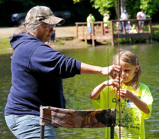 7-year-old Austyn Barnes puts some fresh bait on her hook as her aunt Debbie Pack holds her fishing pole still for her during the 23rd Annual Kids Fishing Derby Saturday morning at Little Beaver State Park. Hundreds of kids 14 and under flocked to the lake area at Little Beaver, some of them already angling veterans while others were getting their first fishing experience.<br /> Brad Davis/The Register-Herald