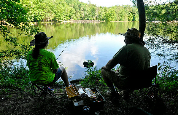 Oak Hill residents Matt Lawhorn and his daughter Lindsey, 14, relax in a nice shady spot farther down along the lake during the 23rd Annual Kids Fishing Derby June 14 at Little Beaver State Park. Lindsey is a six year veteran of the derby, and now that's she's 14 this would be her last one, however she may take up babysitting duties next year so that she can bring a few kids herself, thus staying involved in the event.<br /> Brad Davis/The Register-Herald