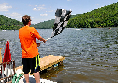 Flag man Logan Sweeney waves the checkered flag as power boats speed past the finish line at the conclusion of a heat race during the Travis Pond Memorial Regatta Saturday afternoon at Bluestone Lake in Hinton. Drivers from all over the country brought their outboard racing boats to Hinton for the Carolina Virginia Racing Association event for a weekend of speed, sun, and competition. Brad Davis/The Register-Herald