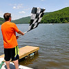 Flag man Logan Sweeney waves the checkered flag as power boats speed past the finish line at the conclusion of a heat race during the Travis Pond Memorial Regatta Saturday afternoon at Bluestone Lake in Hinton. Drivers from all over the country brought their outboard racing boats to Hinton for the Carolina Virginia Racing Association event for a weekend of speed, sun, and competition.<br /> Brad Davis/The Register-Herald