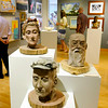 Clay statues by Mercer County artist Amy McPherson sits on display at right as area residents browse different artworks by other artists from the state during the 7th annual Best of West Virginia juried art exhibit Sunday afternoon at Tamarack. <br /> Brad Davis/The Register-Herald