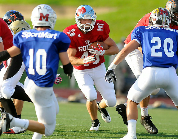 Meadow Bridge's Jake Parker rumbles toward the line of scrimmage as he carries the ball during the North South All-Star game Saturday night in Charleston.<br /> Brad Davis/The Register-Herald