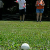 Blue Ridge, Va. resident Ted Puckett plays a game of murbles with Salem, Va. resident Ginger Taylor June 16 at Pipestem State Park. Murbles, a spin-off of the traditional marbles game, can be played just about anywhere. Each player gets three balls of a certain color, known as murbles, and the white point ball, seen here in the foreground, is first tossed forward at any distance. Players then take turns tossing their murbles, trying to get it as close to the point ball as possible. Each ball represents a point, and they are received by the one player who gets the closest to the point ball. The person who gets the points also gets possession of the point ball for the next round, and players can toss it anywhere, whether it's in open ground or in an area with obstacles. The game allows for tons of imagination.<br /> Brad Davis/The Register-Herald