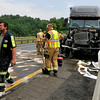 Firemen and cleanup crew clear the area around a semi truck involved in an accident with a cattle truck Friday afternoon on I-64 northbound about one mile past the I-77 split. Three cattle escaped after the accident, two of which had to be put down because they posed a safety threat as they roamed the active highway, while the third was still said to be on the loose somewhere nearby.<br /> Brad Davis/The Register-Herald