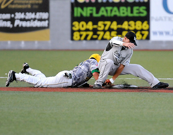 West Virginia's Rob Youngblood, left, barely makes it safely back to the second base bag on a pickoff attempt despite a skillful between-the-legs tag attempt by Lorain County infielder Cody Semler last night at Linda K. Epling Stadium.<br /> Brad Davis/The Register-Herald