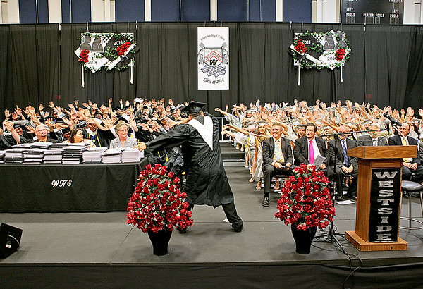 "Westside High School graduating senior Breyer Morgan leads his fellow classmates in one final ""roller coaster"" cheer during the school's commencement ceremony Sunday afternoon in Clear Fork. If you ever attended a Westside sporting event this year, you'd often see Morgan leading the Clear Fork Crazies student section in manuevers just like this one.<br /> Brad Davis/The Register-Herald"