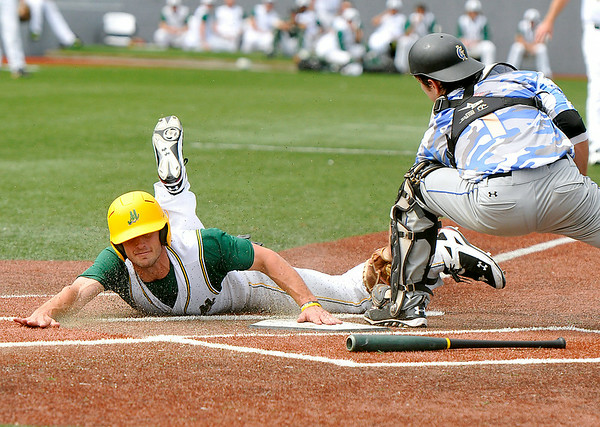 West Virginia's Grant Massey scores the go-ahead run as he beats Champion City catcher Joey Mancuso's tag during the bottom of the 7th inning of the Miners' 5-2 win over the Kings Sunday afternoon at Linda K. Epling Stadium.<br /> Brad Davis/The Register-Herald