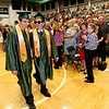 A sunglasses-clad Joey Lupardus, right, makes his way to the stage with fellow graduating senior Charlie McKinney during the opening moments of Wyoming East High School's commencement ceremony Sunday evening in New Richmond.<br /> Brad Davis/The Register-Herald
