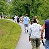 Area residents stretch as far as the eye can see as they march along the White Oak rail trail during the Stop the Violence Walk Saturday morning at the Oak Hill railroad depot. Area residents walked the White Oak rail trail in sporadic rain to show support and solidarity for a woman who was sexually assaulted along the trail last week, and every bit of the proceeds from a raffle and donation drive went to help with her medical expenses. The event was put on by a combination of concerned citizens and the Fayette County Women's Resource Center.<br /> Brad Davis/The Register-Herald
