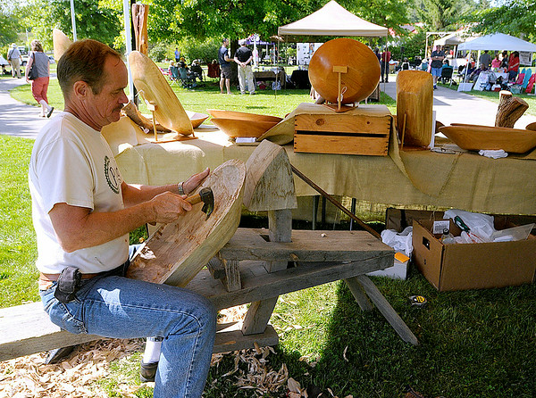Oak Hill resident and proud carver David Bragg uses a hand tool known as a bowl maker's adze to carve out one of his famous wood bowls during Tamarack's Appalachian Music and Art Festival Saturday afternoon. Bragg was just one of several area artisans on hand to demonstrate their crafts, while a number of local bands performed during the course of the eight-hour event, all free of charge.<br /> Brad Davis/The Register-Herald