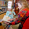 Patience Meadows, 4, who opted to wear her paper Dr. Seuss hat rather than stick it on a balloon, picks out a book to read with her grandmother, Arlene Russell Saturday morning at the Raleigh County Public Library.<br /> Brad Davis/The Register-Herald