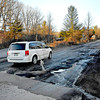 A driver rolls through a bad section of potholes along Stanaford Road, even after steering their vehicle through the opposing lane to avoid the worst of them Friday evening near Lanark. After this year's rough winter, many of the area's roads are left crumbling and in desperate need of patching.<br /> Brad Davis/The Register-Herald