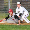 St. Albans' Adam Bowen looks up to see the umpire's safe call after beating the tag by Red Devils third baseman Joey Lokant Friday evening in Oak Hill.<br /> Brad Davis/The Register-Herald