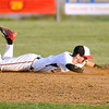 Oak Hill shortstop Ricky Epperly has a sharp ground ball get by him up the middle during the Red Devils' loss to St. Albans Friday evening.<br /> Brad Davis/The Register-Herald