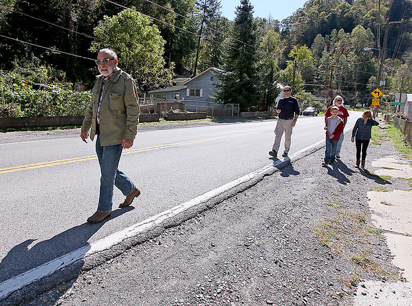 Brad Davis/The Register-Herald<br /> Rocket Boy Roy Lee Cooke, left, leads entusiasts (from left) Grant Mason, his 11-year-old son Reese, David Kurtz and Wendy Holdren on a quick tour of his old neighborhood during a trip to his native Coalwood Sunday afternoon. He was guiding them to the home he moved into just before entering the first grade and where he spent 12 years of his childhood growing up. Cooke was making his first visit to the town since 2011, showing a group of enthusiasts around his old stomping ground telling stories of the Rocket Boys' antics and remembering old times.