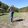 Brad Davis/The Register-Herald<br /> Rocket Boy Roy Lee Cooke looks over the famous field where the gang launched their rockets during a trip his native Coalwood Sunday afternoon. Cooke was making his first visit to since 2011, showing a group of enthusiasts around his old stomping ground telling stories of the group's antics and remembering old times. The shelters at left weren't present in 1957 when the boys began launching, and a railroad that's no longer present ran along a creek hidden in the woods to the left of Cooke that they would sometimes use to walk into the remote area.