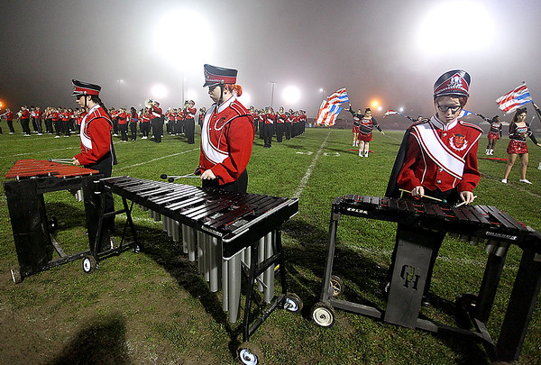 """Brad Davis/The Register-Herald<br /> Oak Hill marching band members (from left) Heather Martin, Meridian Fox and Emily McVicker tap out their notes on xylophones during halftime of the Red Devils' game against Point Pleasant Friday night. The three make up a critical subsection of the percussion group and call themselves """"The Pit."""""""