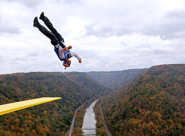 Brad Davis/The Register-Herald<br /> A Red Bull Air Force base jumper spins as he executes a back flip from a diving board during the 35th Annual Bridge Day Saturday morning at the New River Gorge Bridge. Thousands of professional and amateur adrenaline junkies, extreme sports enthusiasts and fans packed the deck of the bridge for a day of thrills mixed in with a few chills in the crisp fall air.