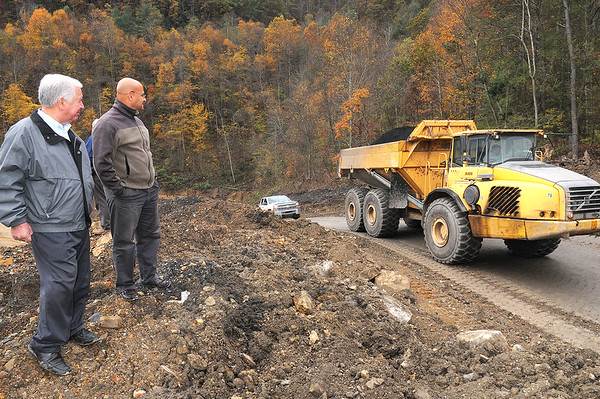 Rick Barbero/The Register-Herald<br /> Congressmen Nick Rahall, left, and Ali Sadeghian, project manager Division of Highway watch a truck hauling coal away during a media tour of the Coalfields Expressway construction site.
