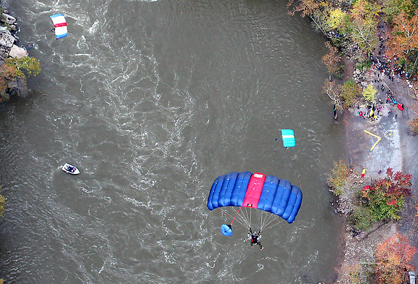 Brad Davis/The Register-Herald<br /> Base jumpers glide toward their target landing zone on the river bank at right during the 35th Annual Bridge Day event Saturday afternoon at the New River Gorge Bridge.