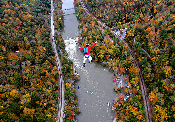 Brad Davis/The Register-Herald<br /> A base jumper plunges toward the New River during the 35th Annual Bridge Day Saturday morning at the New River Gorge Bridge. Thousands of professional and amateur adrenaline junkies, extreme sports enthusiasts and fans packed the deck of the bridge for a day of thrills mixed in with a few chills in the crisp fall air.