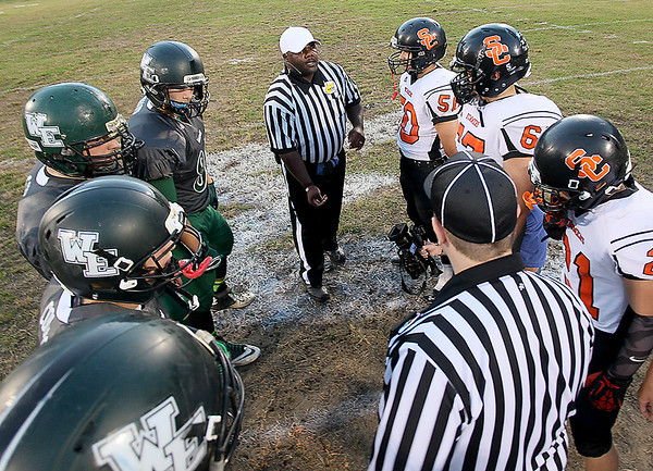 Brad Davis/The Register-Herald<br /> Team captains from Wyoming East and Summers County gather at midfield for the opening coin toss Friday night in New Richmond.