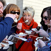 Brad Davis/The Register-Herald<br /> Patrons (from left) Annetta Sharp, Cathy Whitt, Kim Allen, Jamie Runyon and her mother Rena collectively chow down on fresh fruit smothered in chocolate after visiting the fountains at ReMax Vision Quest's storefront during the Lewisburg Chocolate Festival Saturday afternoon.