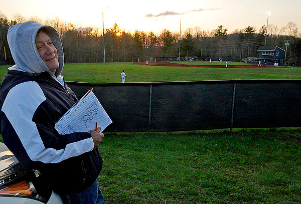 """Brad Davis/The Register-Herald<br /> Shady Spring baseball fan and parent Michael Schack takes in another game from the lofty view along the left field parking lot as the Tigers take on Woodrow Wilson behind him on a chilly but clear Wednesday evening. Schack hasn't missed a single home or away game this year as he watches his son, starting shortstop Brian Schack, during the games and maintains his own score book to keep track of how he's doing as the season progresses. """"It's how I know he's got a 14-game hitting streak going right now,"""" Schack said of Brian's performance up to this point. Last year he had two sons to keep track of, as his older son Brendan played mostly at catcher last year before graduating and heading off to West Virginia Weslyan."""