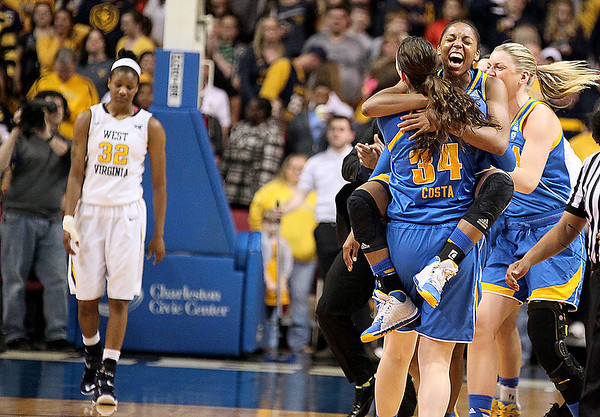 Brad Davis/The Register-Herald<br /> WVU senior Crystal Leary (left) makes her way back to her teammates as UCLA's Nirra Fields leaps into an embrace with teammate Corrine Costa after defeating the Mountaineers in the Women's National Invitation Tournament final Saturday afternoon at the Charleston Civic Center.