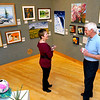 "Brad Davis/The Register-Herald<br /> Putnam County artist Pat Cross, left, chats with Beckley resident and art enthusiast David Rader about some of her work that hangs on the walls around them during the opening day reception for Tamarack's newest exhibit called ""Imparting Art"" Sunday afternoon."