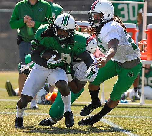 Brad Davis/The Register-Herald<br /> Marshall receiver Deandre Reaves is taken down by linebacker Marquis Couch (behind) and safety Kendall Gant during the Thundering Herd's scrimmage at the Advocare Sports Performance Complex in White Sulphur Springs Saturday afternoon.
