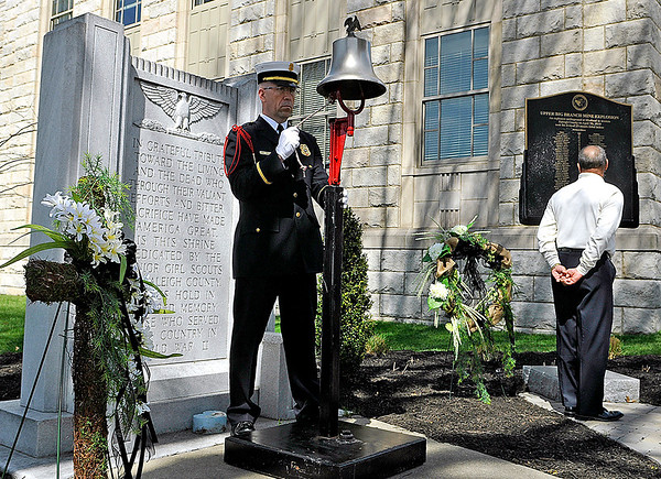 Brad Davis/The Register-Herald<br /> Beckley Fire Department Lieutenant Ernie Parsons rings a bell for each of the 29 miners' names as they're read aloud by relative Kenneth Price (far right) during a memorial ceremony Sunday afternoon in downtown Beckley. The fifth-year anniversary of the Upper Big Branch mine explosion was a somber one, with victims' family members paying respects and shedding tears as they viewed the memorial. Price's brother Joel, a shearer operator, was one of those men.