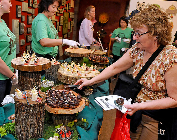 Brad Davis/The Register-Herald<br /> Beckley resident Bettie Worley picks out treats from The Greenbrier Sporting Club's elaborate setup during the Lewisburg Chocolate Festival Saturday afternoon.