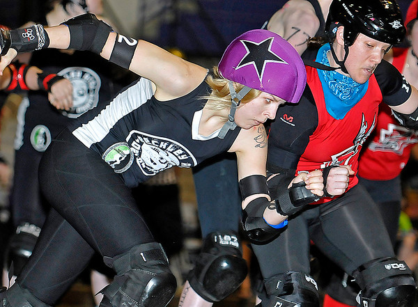 """Brad Davis/The Register-Herald<br /> Beckley Area Derby Dame Kati """"Phyliss Kill'er"""" Grimmett, left, battles her way through traffic against the Eerie Roller Girls during a double header bout night at the Beckley-Raleigh County Convention Center April 18."""