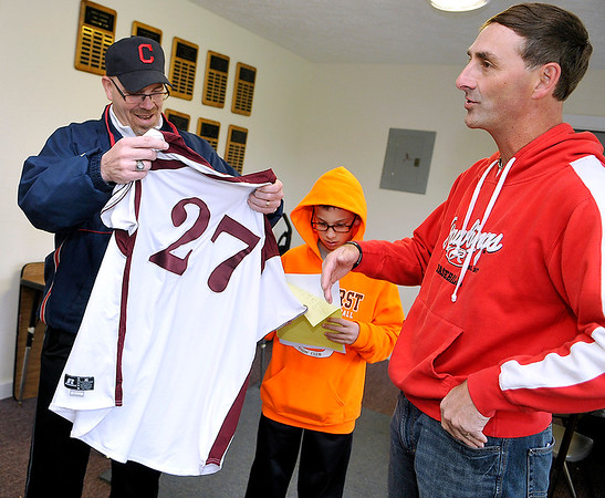 Brad Davis/The Register-Herald<br /> Current Cleveland resident and Woodrow Wilson baseball Hall of Famer Chuck Tate, left, marvels at a Flying Eagles jersey given to him by manager Mark Daniel, right, during a visit to the school inside the baseball field's press box Saturday morning. Tate graduated from Woodrow Wilson in 1983.