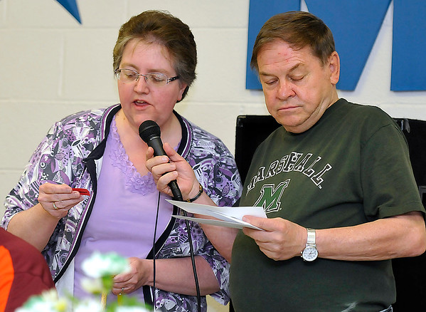 Brad Davis/The Register-Herald<br /> Emcee Pate King and Ronda Stone read off winning tickets for door prizes Wednesday evening in Mullens.
