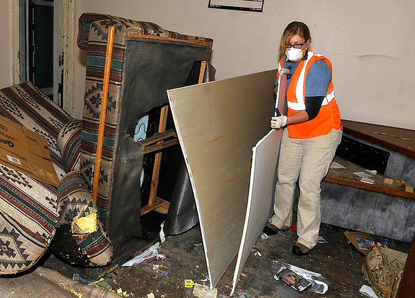 Brad Davis/The Register-Herald<br /> Volunteer Tamie Stein removes materials left inside the historic but dilapidated apartment complex in Helen during the architectural mothballing process Saturday morning.
