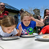 Brad Davis/The Register-Herald<br /> Bluefield sisters Alexis (left), 9, and Amya (middle) Farley, 7, have a little sibling competition as the two participate in the Chocolate Mousse Eating Contest against others in their age group, all while parents and onlookers get a good laugh watching the youngsters try to balance breathing and eating it as fast as possible during the Lewisburg Chocolate Festival Saturday afternoon.
