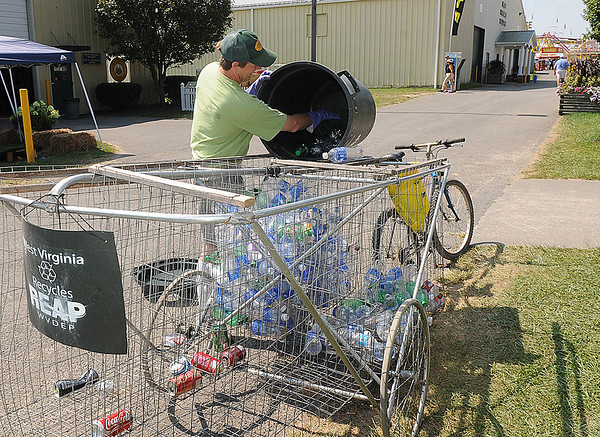 Rick Barbero/The Register-Herald<br /> Matthew Tate collecting recycling plasic bottles and cans on his bike at the State Fair of West Virgina in Fairlea.