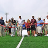 Brad Davis/The Register-Herald<br /> YMCA of Southern West Virginia's Jay Rist (middle in white), Woodrow Wilson girls soccer coach Paulette Lambert (right of Rist) and a collection of local officials and soccer personalities hold the ribbon as Candice Keenan (left of Rist) cuts it during a ceremony for the new field turf surface at the YMCA Paul Cline Memorial Sports Complex Saturday morning. Shortly after the ceremony, the Woodrow Wilson girls team played against Shady Spring.