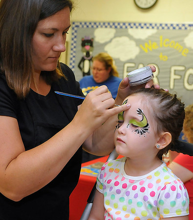 Brad Davis/The Register-Herald<br /> Four-year-old Artie resident Layla Stover keeps still while Serendipity Face Painting's Lacy Treadway gives her a rock star look during a launch party for the Imagination Library Saturday morning at Clear Fork District Elementary.