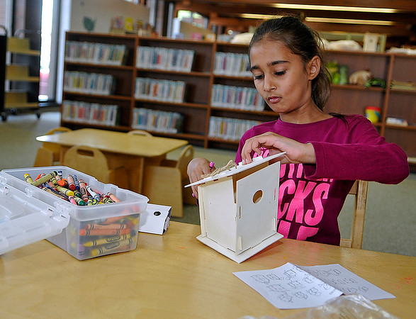 "Brad Davis/The Register-Herald<br /> 8-year-old Beckley resident Amal Rameez puts together a birdhouse during an Appalachian Festival ""birdwatching"" event Saturday morning at the Raleigh County Public Library. To Earn the birdhouse, she first had to scour the library for hidden illustrations of several different song birds found throughout the Appalachian region and mark them off a check list. Once that task was complete, children would receive and decorate a birdhouse and a pair of paper binoculars they can use to watch any future inhabitants of their houses after they took them home."