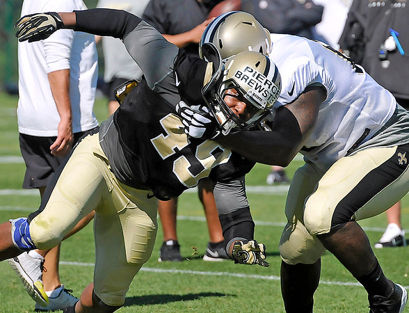 Brad Davis/The Register-Herald<br /> Linebacker Markus Pierce-Brewster, left, tries to power his way around tackle Nick Becton during drills at New Orleans Saints practice Saturday morning in White Sulphur Springs.